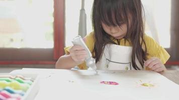 linda chica asiática con camisa amarilla y delantal es un dibujo a mano con pintura brillante multicolor sobre papel blanco en casa. la clase de arte hace que los niños sean creativos. actividades divertidas para mejorar las habilidades escolares. video