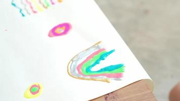 A close-up shot of a child's hand drawing by glitter paint in multi colors and beautiful on white paper It is an art learning, hobbies at home to practice design skill to be creative with happiness. video