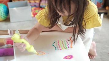 chica asiática con camisa amarilla y delantal está dibujando corazones en forma de pintura brillante multicolor sobre papel blanco en casa. la clase de arte hace que los niños sean creativos. actividades lúdicas para mejorar las habilidades escolares. video