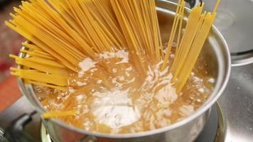 Raw spaghetti is being cooked in boiling water in a kitchen pot. video