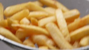 Close-up of hand sprinkled with salt on french fries. video
