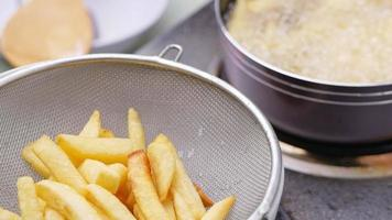 Frying french fries in the fryer in hot oil on the electric stove. video