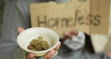 sin hogar con ropa sucia con un cartel video