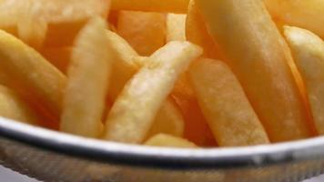 Close up of french fries in a basket to drain the oil. video