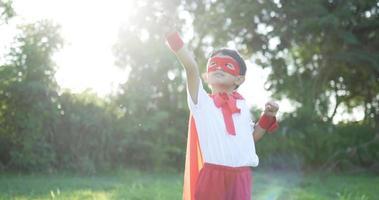 menino herói em vermelho no jardim voando video