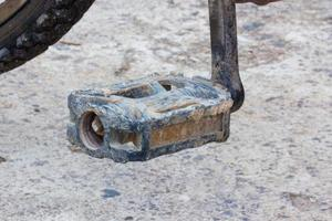 Detalle del viejo pedal de bicicleta usada con barro seco foto