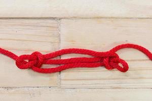 nudo sheepshank hecho con cuerda roja sobre fondo de madera. foto
