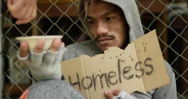 Persona sin hogar con ropa sucia sosteniendo la taza de cambio video