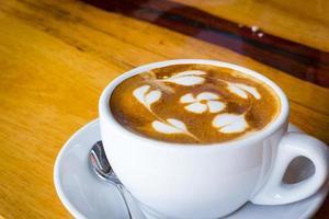 café caliente con flor de espuma de leche sobre mesa de madera. foto