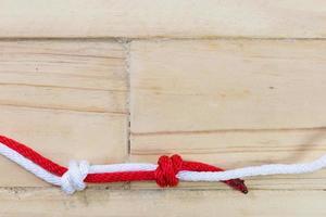 nudo de pescador hecho con cuerda roja sobre fondo de madera. foto