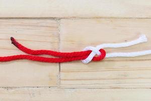 Hoja de nudo doblado hecho con cuerda roja sobre fondo de madera. foto