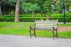 metal garden chair on concrete ground with green grass behind. photo