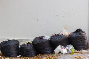 bolsas negras de basura y waiste en la pared sucia en blanco. foto