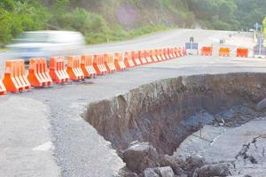 Carretera agrietada después del terremoto con barricada amarilla. foto