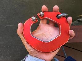 foto horizontal del mosquetón rojo grande en la mano izquierda del hombre.
