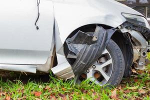 closeup damaged front wheel and bumper on green grass, safety concept photo