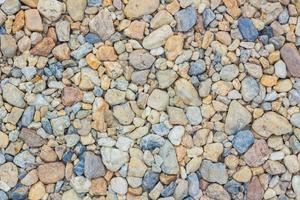 Textura de piedras de cantos rodados de colores en el suelo foto