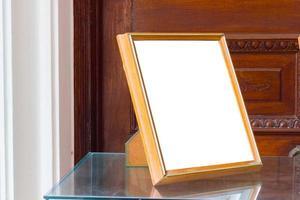 Marco de fotos en blanco aislado sobre la mesa de cristal