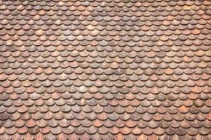 Old grunge red and orange weathered roof tiles texture background. photo