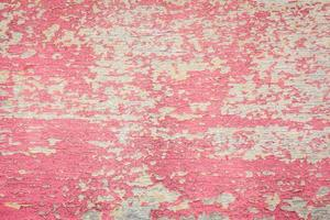 pintura roja agrietada sobre fondo de madera descolorida. foto