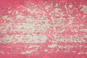 pintura roja descascarada sobre fondo de madera descolorida. foto