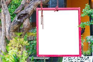 marco rojo aislado colgado de un árbol en un jardín exuberante, trazado de recorte. foto