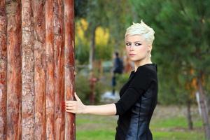 mujer rubia cerca de la pared de madera foto