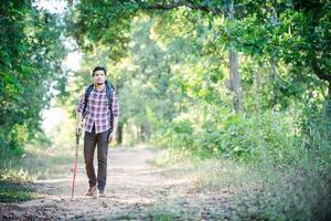 Hombre joven inconformista caminando por el camino rural durante caminatas de vacaciones. foto