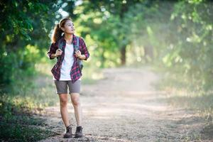 Young woman hiker with backpack walking and smiling on a country trail photo