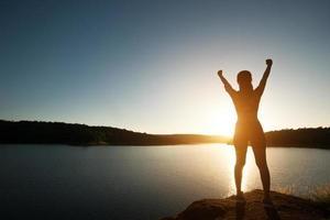 silueta de mujer lograr senderismo en la cima con vista al lago al atardecer. foto