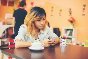Close-up of woman text messaging with her mobile at coffee shop. photo