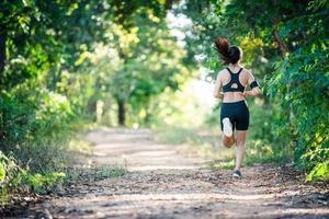 mujer joven fitness corriendo en un camino rural. mujer deportiva corriendo. foto