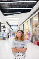 Young beautiful woman standing thinking something at shopping mall. photo