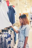 mujer joven feliz mirando venta de ropa en la tienda. foto