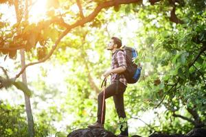 Joven excursionista relajándose en la cima de una montaña, disfruta de la naturaleza y la aventura foto