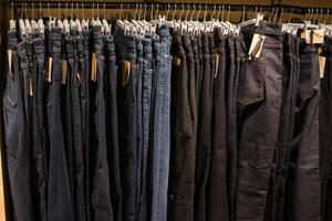 Jeans on clothes rail in clothing store at shopping mall. photo