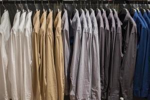 Shirt hanging on rail at Clothes shop. photo