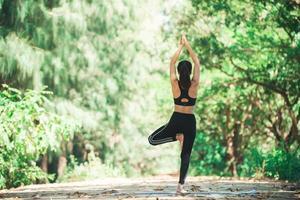joven asiática haciendo yoga por la mañana en el parque. saludable foto