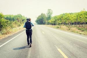 mujer joven haciendo autostop con mochila caminando por la carretera. foto