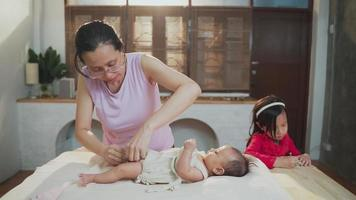 mère asiatique nettoyage nouveau-né avec sa fille à la maison video