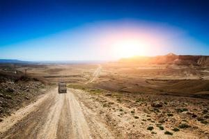 Jeep in a desert road photo