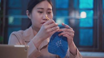 Asian woman doing hobby by sewing and knitting a crochet handmade video