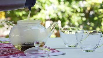 feche as mãos das pessoas derramando água quente no bule para fazer chá video