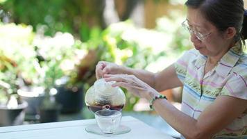 mulher asiática sênior servindo chá preto de um bule de chá em um copo no jardim video