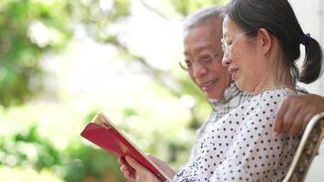casal sênior rindo enquanto assiste mídias sociais em um tablet em casa video