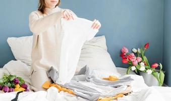 Mujer joven organizando ropa sentada en la cama en casa foto