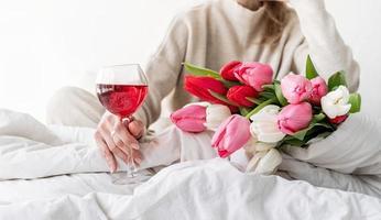 Mujer sentada en la copa de vino y flores de tulipán foto