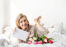 woman lying on the bed holding tulip flowers bouquet and blank card photo