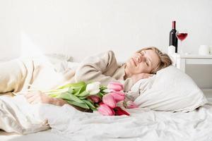 Mujer acostada en la cama en pijama con ramo de flores de tulipán foto
