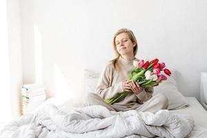 mujer sentada en la cama en pijama sosteniendo flores de tulipán foto